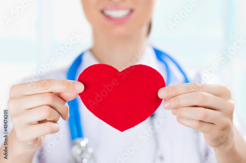Female doctor with stethoscope holding red human heart at hospit