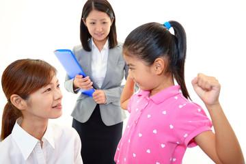 笑顔の親子と女性教師