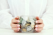 Woman hands with money in glass jar, close up