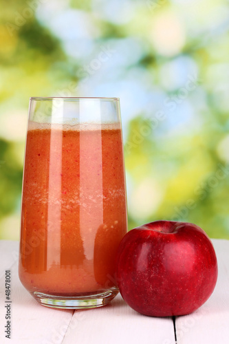 Glass of fresh apple juice on wooden table, on green background