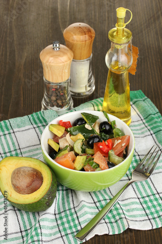 Tasty avocado salad in bowl   surrounded by spices