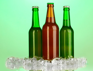 Beer bottles in ice on green background