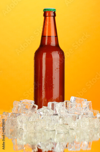 Beer bottle in ice on orange background