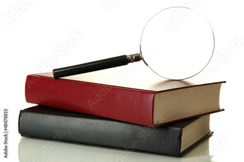 Magnifying glass and books isolated on white