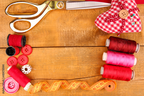 Sewing accessories and fabric on wooden table close-up