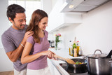 Woman making dinner with partner watching
