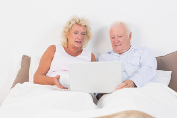 Aged couple reading or using a tablet
