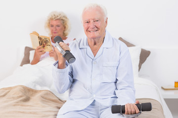 Elderly man lifting hand weights