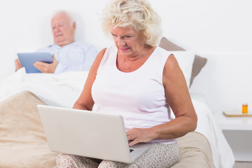 Aged couple using a tablet and the laptop