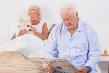 Old couple reading on the bed