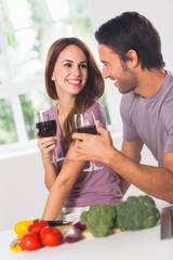 Smiling lovers with wine and vegetables