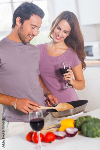 Couple preparing food and drinking