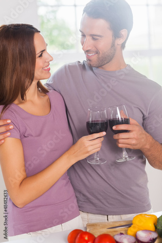 Lovers toasting standing with a glass of wine