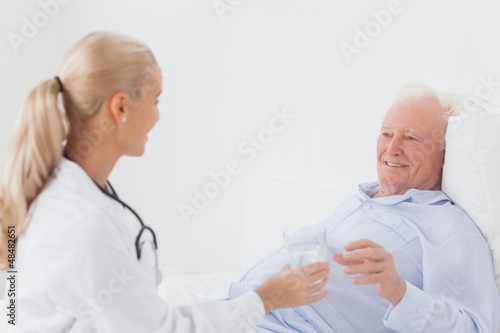 Doctor handing glass of water to patient