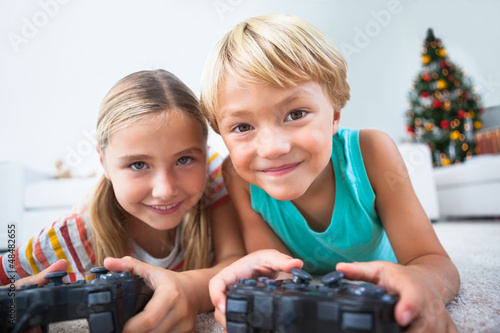 Happy siblings playing video games on floor