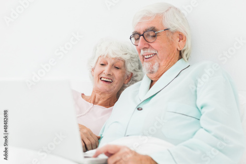 Couple watching something on laptop in bed
