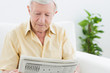 Elderly calm man reading newspapers
