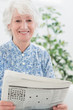 Elderly smiling woman reading newspapers