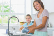 Happy mother and daughter doing the washing up