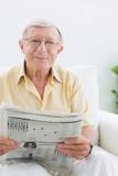 Smiling elderly man reading the news