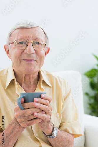 Elderly man looking at camera with a cup
