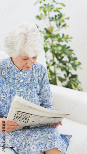 Elderly cheerful woman reading newspapers
