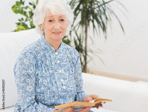 Elderly cheerful woman reading a old novel