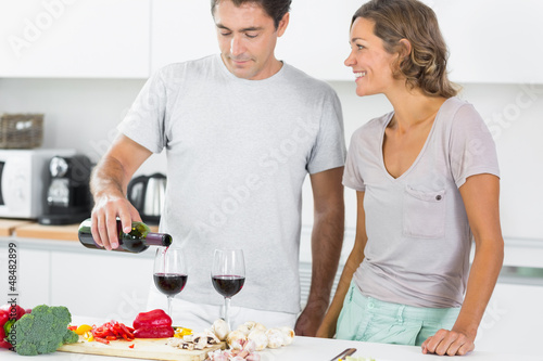 Husband pouring red wine in kitchen