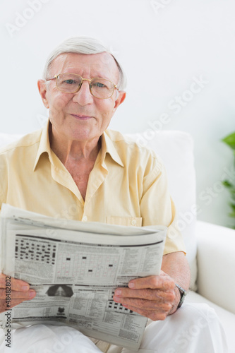 Smiling elderly man reading the news