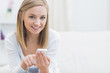 Portrait of happy woman with mobile phone at home