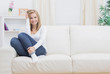 Casual happy woman sitting on sofa