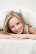 Close-up portrait of beautiful woman under sheet in bed