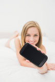 Woman showing you her new smartphone in bed