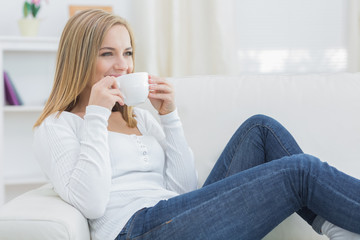Woman drinking coffee as she looks away on couch