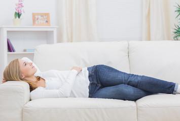 Casual thoughtful woman lying on sofa