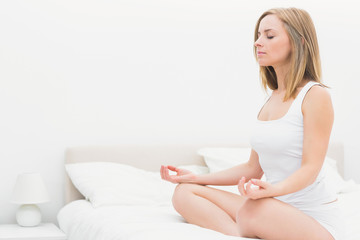 Woman sitting in lotus position with eyes on bed