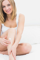 Woman applying cream on leg while sitting on bed