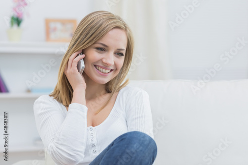 Casual young woman using mobile phone at home