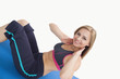 Portrait of happy young woman doing sit-ups on exercise mat