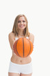 Happy woman in sportswear holding out basketball