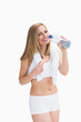 Portrait of smiling woman with towel around neck drinking water