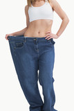 Young woman wearing old pants after losing weight