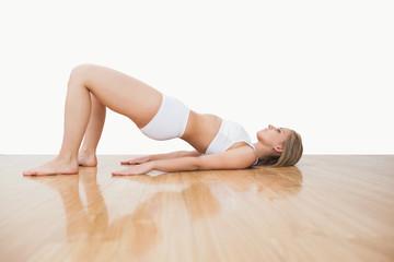 Side view of woman in yoga pose on hardwood floor
