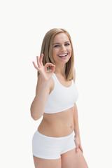 Portrait of happy woman in sportswear gesturing okay sign