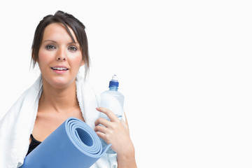 Portrait of woman holding water bottle and exercise mat