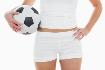 Midsection of fit woman in sportswear with football