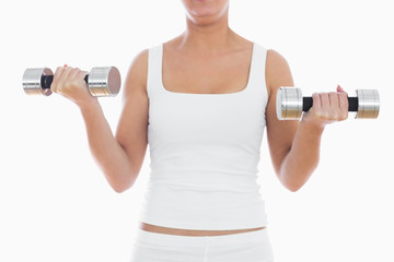 Midsection of woman exercising with dumbbells
