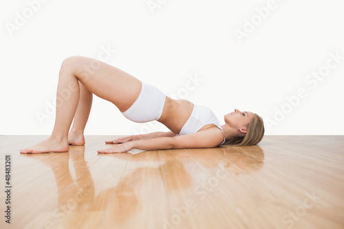 Side view of woman in yoga pose on hardwood floor