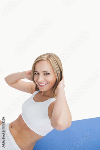 Portrait of happy woman doing sit-ups on exercise mat