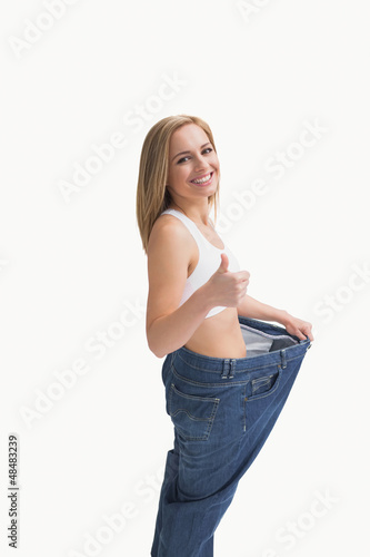 Woman wearing old pants after losing weight and gesturing thumbs